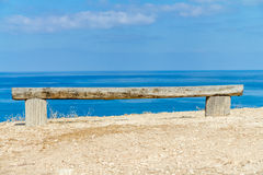 Handmade Wooden Bench by the Sea. Bench made of wooden logs on the beach near the sea Royalty Free Stock Images
