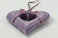 Handmade wooden heart. Handmade wooden purple heart old style on light background Royalty Free Stock Photo