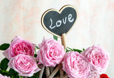 Handmade wooden heart among red and pink roses Royalty Free Stock Photography