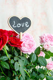 Handmade wooden heart among red and pink roses Stock Images