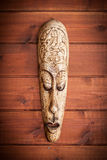 Handmade wooden mask, carved with lizards. On wooden surface Stock Images