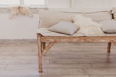 Handmade wooden sofa in bright room, soft pillows royalty free stock photo