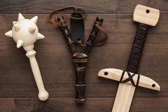 Handmade wooden training toy sword, mace and slingshot Royalty Free Stock Images