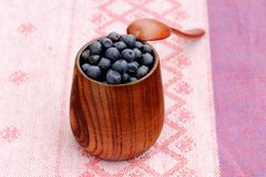 Handmade wooden vase full with fresh wild blueberries with woode Royalty Free Stock Image