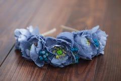 Handmade wraith of blue flowers lying on wooden background Stock Image