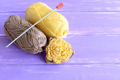Handmade yellow and brown crochet flower decorated with beads. Two skeins of cotton yarn and crochet hook on wooden background Royalty Free Stock Photography