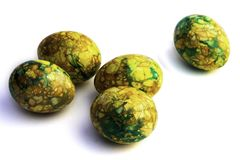 Handmade yellow green easter eggs painted marbled over white background royalty free stock image