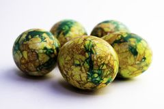 Handmade yellow green easter eggs painted marbled over white background stock photo