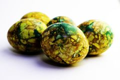 Handmade yellow green easter eggs painted marbled over white background royalty free stock photos