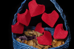 Handmaid busket with origami hearts for Saint Valentine`s Day closeup. Handmaid blue busket with bright red origami hearts for Saint Valentine`s Day on black Stock Photos
