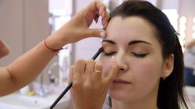 Handmake-upkünstler wendete Make-up auf dem Gesicht einer jungen Frau an Mädchen, das Augenmake-up in einem Berufssalon tut abend stock footage