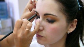 Handmake-upk?nstler wendete Make-up auf dem Gesicht einer jungen Frau an M?dchen, das Augenmake-up in einem Berufssalon tut abend stock footage