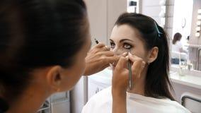 Handmake-upk?nstler wendete Make-up auf dem Gesicht einer jungen Frau an M?dchen, das Augenmake-up in einem Berufssalon tut abend stock video