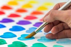 Handmalerei-Aquarellherzen mit einem Malerpinsel Stockfoto