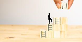 Handmanförsök att sätta den nästa trappan på trätärningen till mannen för nästa steget, möjlighet, jobb, affär, framgång, projekt arkivbild