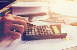 Handmens die op calculator met berekening over belastingsannua drukken stock afbeeldingen