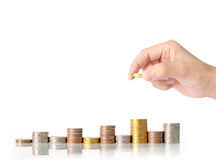 Handmenschliche Hand, die Münze zum Geld setzt Stockbilder