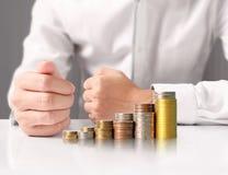 Handmenschliche Hand, die Münze zum Geld setzt Stockfotos