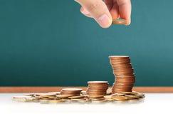 Handmenschliche Hand, die Münze zum Geld setzt Stockfoto