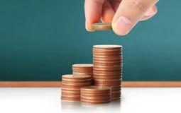 Handmenschliche Hand, die Münze zum Geld setzt Lizenzfreies Stockbild