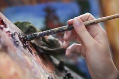 Handmischende Farben auf Palette mit Malerpinsel Stockfotos