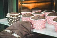Handnehmen-Schokoladenkleiner kuchen weg vom Ofen lizenzfreie stockfotografie