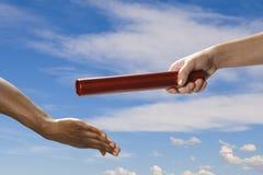 Handoff del bastone del relè con il cielo Fotografie Stock Libere da Diritti