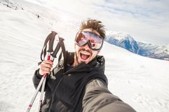 Handome skier in the snow taking a selfie on a mountain. stock photos