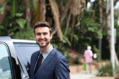 Handomse-Fahrer außerhalb seines Fahrzeuglächelns Stockfotos