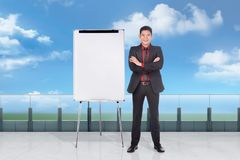 Handosme asian businessman standing with empty whiteboard. Outside office room stock image