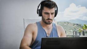 Handosme Man Working at Home at Laptop Computer stock image