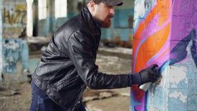 Handosme-Mann-Graffitikünstler wird auf Malereilinien mit Aerosolfarbe auf Spalte im alten leeren Haus konzentriert stock video