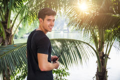 Handosome young man near palm trees Stock Images