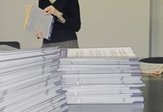 Handout Pamphlets. Piles of Handout Pamphlets and Woman in Background Stock Images