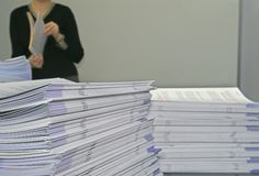 Handout Pamphlets. Piles of Handout Pamphlets and Woman in Background royalty free stock image