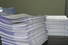 Handout Pamphlets. Piles of handout papers lying on a table Stock Photo