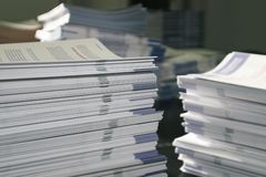 Handout Paper Piles. Piles of handout papers lying on a table royalty free stock photo