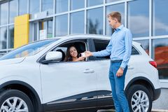 Handover of car keys in a dealership. Buying a new car. The girl bought herself a beautiful new car. The concept of buying a new car Royalty Free Stock Photos