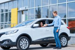 Handover of car keys in a dealership. Buying a new car. The girl bought herself a beautiful new car. The concept of buying a new car Royalty Free Stock Image