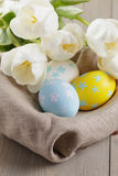 Handpainted easter eggs and white tulips on wood royalty free stock photography