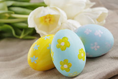 Handpainted easter eggs and white tulips on wood stock photo