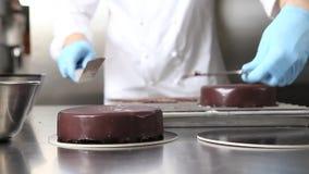 Handpatissier bereitet einen Kuchen, bedecken die auslaufende Schokoladenzuckerglasur vor und arbeitet an Küchen-Arbeitsspitze de stock video footage