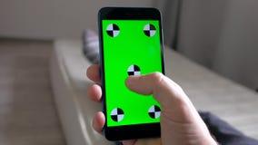 Handpersoon het typen in smartphone met het groene scherm die op matras in ruimte liggen stock video