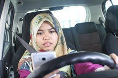 Handphone musulmano della tenuta della donna mentre guidando fotografia stock libera da diritti