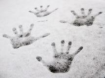 Handprint av de fyra händerna i snön ett olikt format, en vit snötexturnärbild arkivbild
