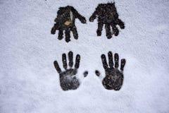 Handprint av de fyra händerna i snön ett olikt format, en vit snötexturnärbild ovanlig vinkel, original royaltyfri foto