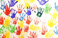 Handprint in multiple color. Multiple colorful children handprints on white canvas stock photography