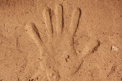Handprint in sand. Hand imprint in sand which looks raised due to lighting Stock Images