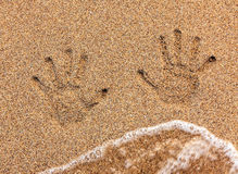 Handprint on sand being washed away Royalty Free Stock Images