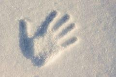 Handprint sur le blanc avec une tonalité bleue de neige avec un hiver d ensoleillé Photographie stock libre de droits